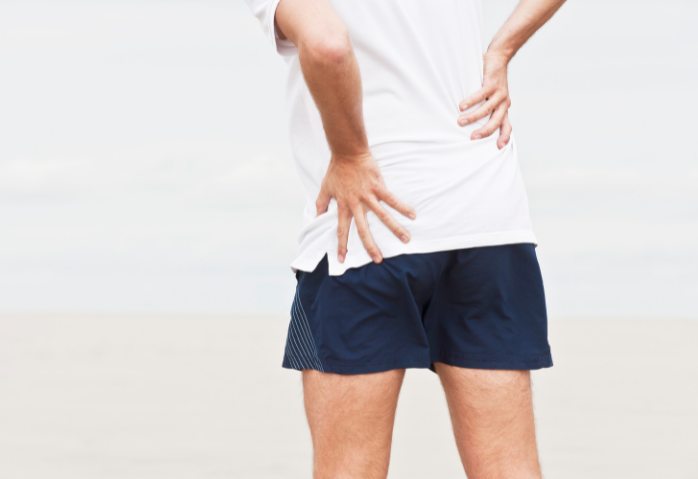 Runner with hip pain, hands on hips