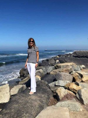 Colette Amit in rocks at the ocean